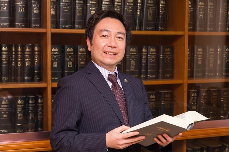六法全書の本棚前に立つ朝日中央綜合法律事務所の弁護士